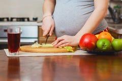 Mujer embarazada hermosa en cocina Fotos de archivo libres de regalías