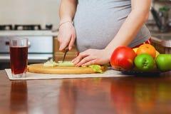 Mujer embarazada hermosa en cocina Foto de archivo libre de regalías