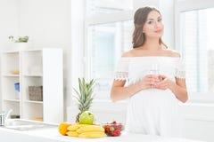 Mujer embarazada hermosa en la cocina que tiene un vidrio de agua Imágenes de archivo libres de regalías