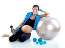 Mujer embarazada hermosa en la gimnasia de la aptitud relajada Foto de archivo