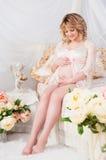 Mujer embarazada hermosa en una bata de casa del cordón que se sienta en una cama de flores Fotos de archivo libres de regalías