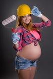 Mujer embarazada hermosa joven en el casco del constructor con la pintura b Fotografía de archivo
