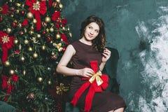 Mujer embarazada hermosa joven en la Navidad con un tre hermoso Fotografía de archivo libre de regalías