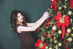 Mujer embarazada hermosa joven en la Navidad con un tre hermoso Imágenes de archivo libres de regalías