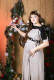 Mujer embarazada hermosa joven en un vestido largo cerca del Año Nuevo tr Imagenes de archivo