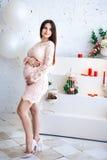 Mujer embarazada hermosa joven en vestido rosado que abraza el vientre con sus manos, contra la perspectiva de una pared de ladri Fotos de archivo