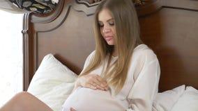 Mujer embarazada hermosa, joven que frota ligeramente su vientre que miente en cama 4K C?mara lenta almacen de metraje de vídeo