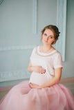 Mujer embarazada hermosa joven que presenta cerca de ventana Fotografía de archivo libre de regalías