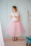 Mujer embarazada hermosa joven que presenta cerca de ventana Foto de archivo