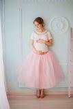 Mujer embarazada hermosa joven que presenta cerca de ventana Fotografía de archivo