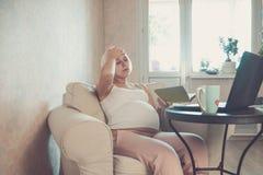 Mujer embarazada hermosa joven que trabaja en el ordenador portátil Mujer de negocios embarazada que busca la información y compr imagenes de archivo