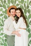 Mujer embarazada hermosa joven y su marido en la situación del sombrero cerca de la pared del cactus imagen de archivo libre de regalías