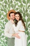 Mujer embarazada hermosa joven y su marido en la situación del sombrero cerca de la pared del cactus imagenes de archivo