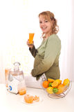 Mujer embarazada hermosa que bebe el zumo de naranja Fotos de archivo