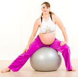 Mujer embarazada hermosa que hace ejercicios en bola Imagen de archivo libre de regalías