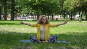 Mujer embarazada hermosa que hace yoga prenatal en la naturaleza al aire libre Deporte, aptitud, forma de vida sana mientras que  metrajes