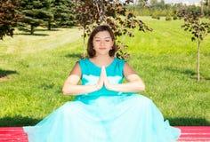 Mujer embarazada hermosa que medita con el vientre grande imagen de archivo