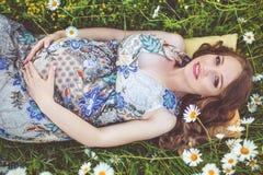 Mujer embarazada hermosa que miente en el campo de la manzanilla Imagenes de archivo
