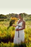 Mujer embarazada hermosa que se relaja en el parque Foto de archivo libre de regalías