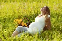 Mujer embarazada hermosa que se relaja en el parque fotografía de archivo