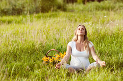 Mujer embarazada hermosa que se relaja en el parque imagenes de archivo