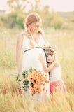 Mujer embarazada hermosa que se relaja en el parque Imagen de archivo libre de regalías