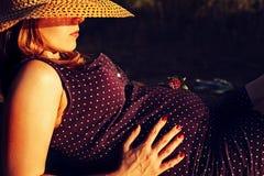 Mujer embarazada hermosa que se relaja en el parque fotos de archivo