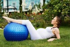 Mujer embarazada hermosa que se relaja en el parque Foto de archivo
