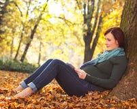 Mujer embarazada hermosa que se sienta en parque Imagen de archivo libre de regalías