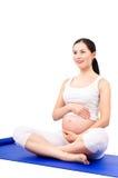 Mujer embarazada hermosa que se sienta en una estera de la yoga Imágenes de archivo libres de regalías
