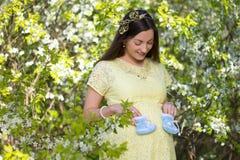 Mujer embarazada hermosa soñadora en jardín floreciente de la cereza Imagenes de archivo