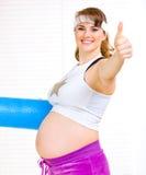 Mujer embarazada hermosa sonriente con la estera del ejercicio Imágenes de archivo libres de regalías