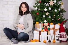 Mujer embarazada joven feliz con el árbol de navidad foto de archivo