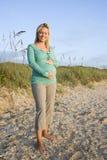 Mujer embarazada joven feliz que se coloca en la playa fotografía de archivo libre de regalías