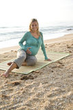 Mujer embarazada joven feliz que se sienta en la estera en la playa fotografía de archivo libre de regalías