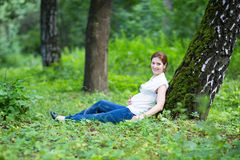 Mujer embarazada joven hermosa que se relaja en un parque Imagenes de archivo