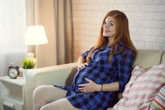 Mujer embarazada joven pelirroja que se sienta en casa en el sofá y fotografía de archivo