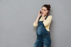 Mujer embarazada joven preocupante que habla en el teléfono móvil Foto de archivo libre de regalías