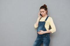 Mujer embarazada joven preocupante que habla en el teléfono móvil Imagenes de archivo