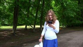 Mujer embarazada linda sonriente con el sombrero y el teléfono en sus manos que camina en parque metrajes