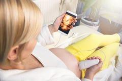 Mujer embarazada moderna que se sienta en un sof? blanco en casa que relaja y que hace sola el ultrasonido digital 3D imagen de archivo
