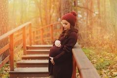 Mujer embarazada pensativa en equipo acogedor suavemente caliente del marsala que camina al aire libre fotos de archivo libres de regalías
