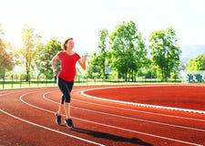 Mujer embarazada que activa en pista corriente en estadio Imagen de archivo