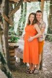Mujer embarazada que almuerza con su marido en un bosque Foto de archivo libre de regalías