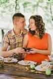 Mujer embarazada que almuerza con su marido en un bosque Fotos de archivo libres de regalías