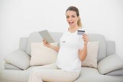 Mujer embarazada que anima que muestra su tableta y tarjeta de crédito que miran la cámara Fotos de archivo libres de regalías