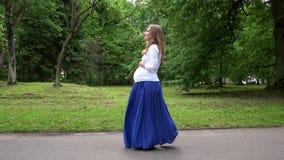 Mujer embarazada que camina en parque el verano almacen de video
