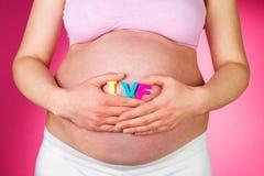 Mujer embarazada que celebra las letras de IVF en fondo rosado Fotografía de archivo libre de regalías