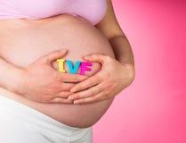 Mujer embarazada que celebra las letras de IVF en un rosa Imagen de archivo libre de regalías