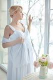 Mujer embarazada que coloca la ventana cercana Imágenes de archivo libres de regalías
